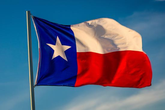 """TEXAS STATE FLAG - Texas """"Lone Star"""" flag stands out against a cloudless blue sky as it flys in...--Photographic Print"""