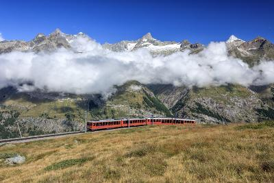 The Bahn Train on its Route with High Peaks and Mountain Range in the Background, Switzerland-Roberto Moiola-Photographic Print