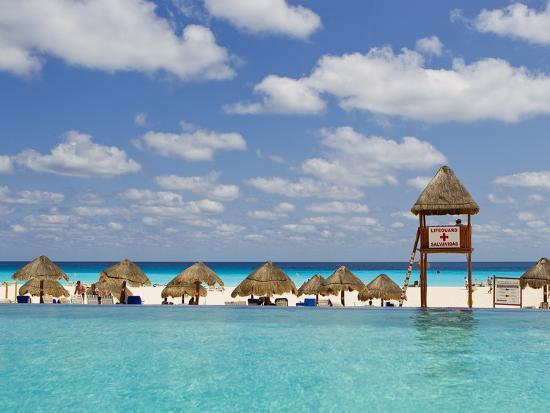 The Caribbean Sea, Tiki Huts and a Lifeguard Stand from a Resort Pool-Mike Theiss-Photographic Print