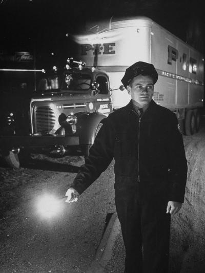 The Driver Placing a Flare on the Dark Road Where the Truck Is Stalled--Photographic Print