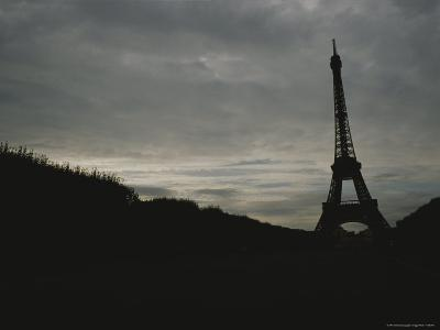 The Eiffel Tower Silhouetted against a Gray, Cloud-Filled Sky-Raul Touzon-Photographic Print
