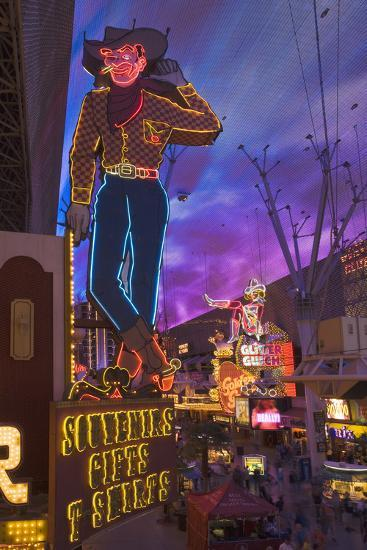 The Famous Ivegas Vici Neon Cowboy Stands among Other Signs on Fremont Street in the Iglitter Gulch-David Davis-Photographic Print