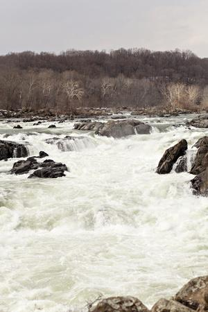 https://imgc.artprintimages.com/img/print/the-fast-moving-waters-of-the-potomac-river-cascade-over-boulders_u-l-pwdr9f0.jpg?p=0