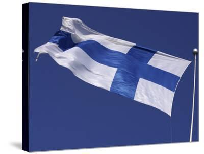 The Flag of Finland on White Fabric with a Blue Cross Against Blue Sky