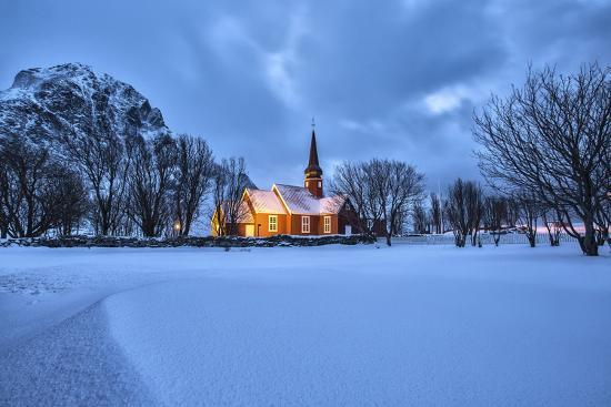 The illuminated church at dusk in the cold snowy landscape at Flakstad Lofoten Norway Europe-ClickAlps-Photographic Print