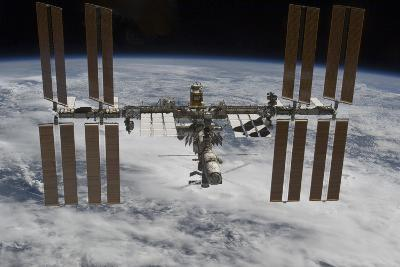 The International Space Station Backdropped Against Clouds over Earth--Photographic Print