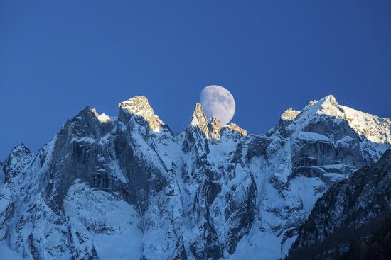 The Moon Appears Behind the Snowy Mountains Illuminating the Peaks-Roberto Moiola-Photographic Print