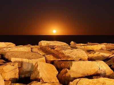 The Moon Rising Behind Rocks Lit by a Nearby Fire in Miramar, Argentina-Stocktrek Images-Photographic Print