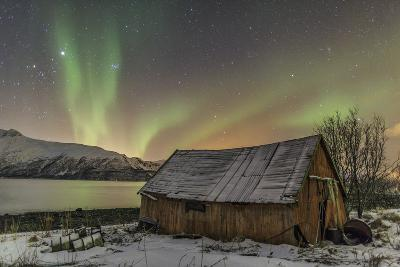 The Northern Lights Illuminates the Wooden Cabin, Svensby, Lyngen Alps, Troms, Lapland, Norway-Roberto Moiola-Photographic Print