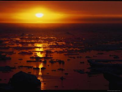 The Setting Sun Reflected on Water Dotted with Chunks of Ice-Norbert Rosing-Photographic Print