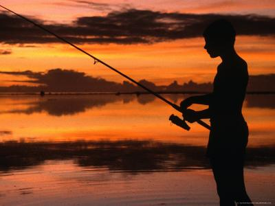 The Silhouette of a Boy Fishing at Sunset in One of the Lagoons Around the Island, Cook Islands-Dallas Stribley-Photographic Print