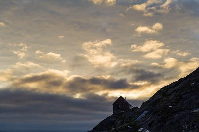 The Silhouette of a Cottage Perched on a Rocky Outcrop on an Arctic Island-Jason Edwards-Photographic Print