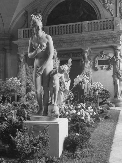 The Statue of Aphrodite and Eros in Louvre Museum During a Flower Show-Dmitri Kessel-Photographic Print