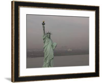 The Statue of Liberty Against a Cityscape in Smog--Framed Photographic Print