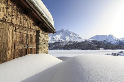 The Sun, Covered by Thin Clouds, Illuminating a Typical Hut Covered with Snow at the Maloja Pass-Roberto Moiola-Photographic Print