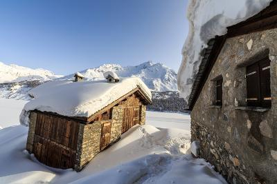 The Sun, Covered with Thin Clouds, Illuminating a Typical Hut Covered with Snow at the Maloja Pass-Roberto Moiola-Photographic Print