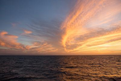 The Sun Rises Above the Horizon and Illuminates Clouds Above the Waters, Isla Coiba National Park-Eric Kruszewski-Photographic Print