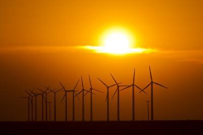 The Sun Sets Behind a Row of Spinning Windmills or Wind Turbines-Mike Theiss-Photographic Print