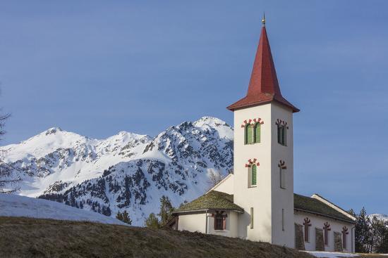 The white alpine church framed by snowy peaks, Maloja, Bregaglia Valley, Canton of Graubunden, Enga-Roberto Moiola-Photographic Print