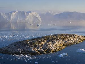 Small Rocky Island and Icebergs by Theo Allofs