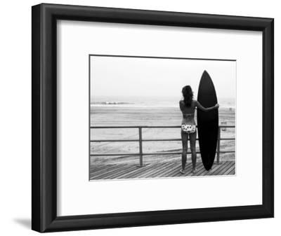 Model with Black Surfboard Standing on Boardwalk and Watching Wave on Beach