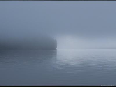 Thick Fog Hangs Over Eerily Calm Water Where a Point of Land Juts Out-Bill Curtsinger-Photographic Print