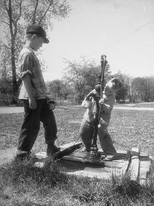 Two Boys Getting Water from a Pump at Rural School by Thomas D. Mcavoy