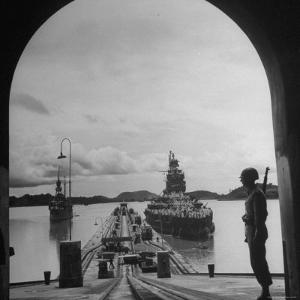 US Soldier Standing Guard over Section of Panama Canal, Battleship with Full Crew on Deck by Thomas D. Mcavoy