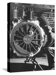Welder with an Acetylene Torch Cutting Through Some of the Old Tubes in a Modern Locomotive by Thomas D. Mcavoy