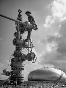 Workman Standing on Machinery at Natural Gas Plant by Thomas D. Mcavoy