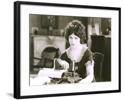 Thoughtful Businesswoman with Typewriter at Desk in Office--Framed Photo