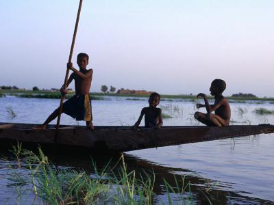 Three Boys Play on a Canoe (Pirogue) on the River in Mopti-Dan Herrick-Photographic Print