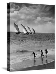 Three Boys Running Along Beach, Following Four Sailboats Out on Ocean