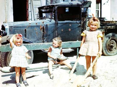 Three Girls Playing in the Sand Next to a War-Damaged Vehicle, Cherbourg, France, July 1944--Photographic Print