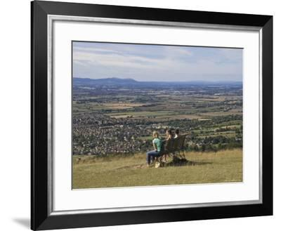 Three Girls Sitting on Bench Looking at View Over Bishops Cleeve Village, the Cotswolds, England-David Hughes-Framed Photographic Print