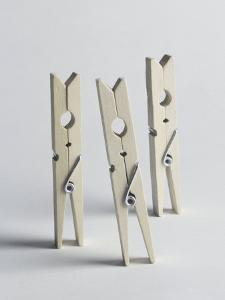 Three Wooden Laundry Pegs Standing Upright