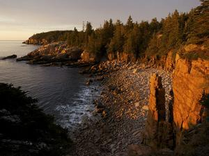 The First Rays of Sunrise on Monument Cove and its Namesake Rock Pillar by Tim Laman