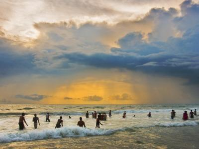 Indian Bathers Playing in Surf During Cloudy Sunset