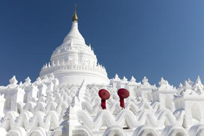 Two young Buddhist monks stand on the white walls of Hsinbyume Pagoda holding red umbrellas, Mingun