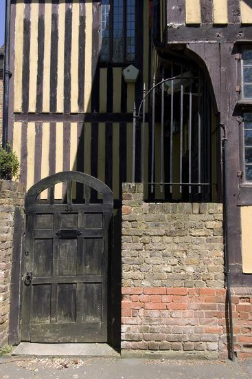 Timber Framed Building with Gate and Brick Wall in Tudor-Style House-Natalie Tepper-Photo
