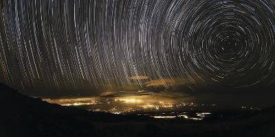 Time-Exposure Image of Star Trails Above a Town on Maui, Hawaii-Babak Tafreshi-Photographic Print