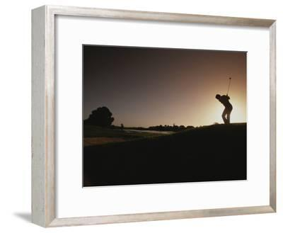 A Man Plays a Game of Golf at Twilight