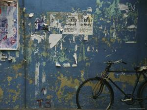 A Bicycle is Parked against a Blue Wall by Todd Gipstein