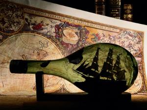 An Antique Map Provides the Backdrop for a Ship in a Bottle by Todd Gipstein