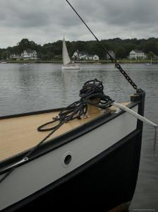 Bow of a Boat with a Sailboat in the Background on the Mystic River, Connecticut by Todd Gipstein