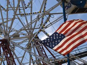 Flag in Front of a Ferris Wheel Against a Summer Sky by Todd Gipstein