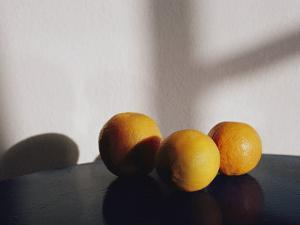 Still Life of Three Oranges on a Table by Todd Gipstein