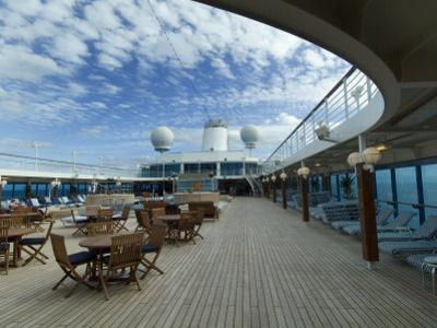 Tables and Chairs on the Pool Deck of a Cruise Ship by Todd Gipstein