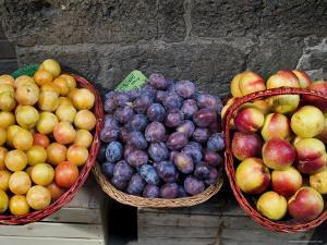 Three Baskets of Colorful Fruit at a Market in Siena, Tuscany, Italy by Todd Gipstein
