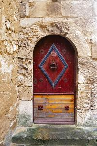 Colorful door in the stone wall of a chateau in France. by Tom Haseltine